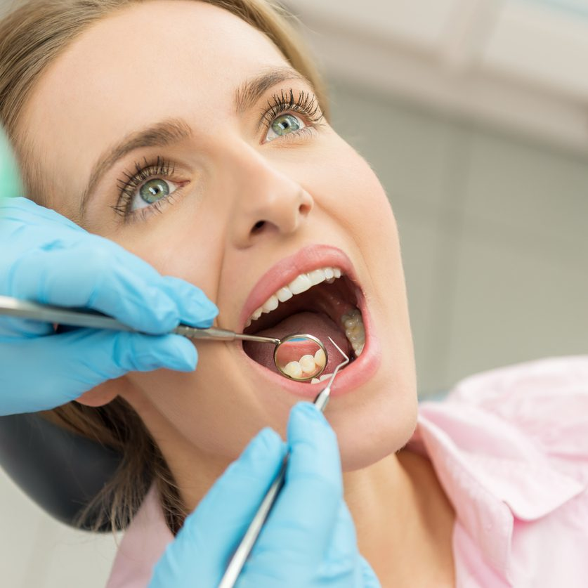 Horizontal color close-up headshot of beautiful woman having dental examination.